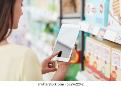 Young woman shopping at the supermarket and checking offers on the digital tablet, technology and consumerism concept