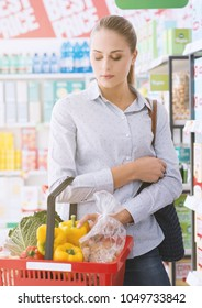 Young woman shopping at the supermarket, she is carrying a grocery basket filled with fresh vegetables