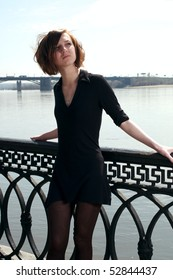 Young woman in short black dress near the river