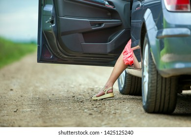Young woman in short dress getting out car with open door on sunny blurred rural road background.