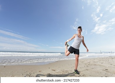 young woman with short hair doing stretching exercise on the beach on a sunny day