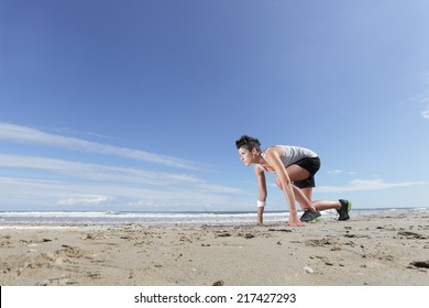 young woman with short hair getting ready for run in the starting position on the beach