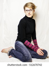 Young woman with short hair and glasses sitting in front of a white background