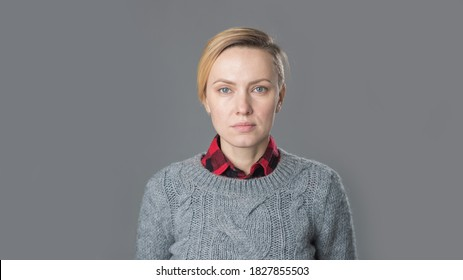 young woman with short hair, natural makeup over light grey background. Indoor portrait of beautiful blonde young woman in knitted sweater
