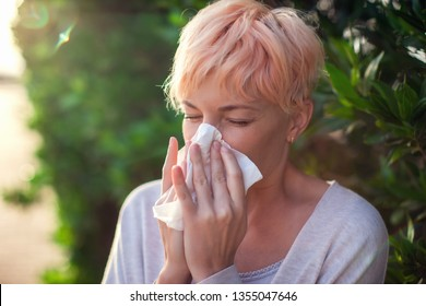 Young woman with short hair sneezing into tissue. flu, allergy, runny nose. People and healthcare concept