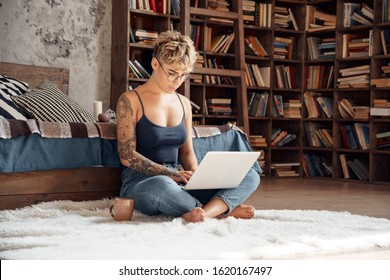 Young woman short hair wearing eyeglasses sitting on fluffy carpet with cup of hot coffee and laptop working online concentrated freelance side hustle