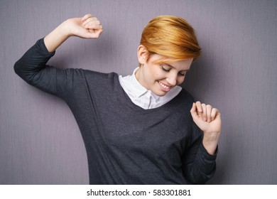 Young woman with short haircut in dark sweater standing against purple wall making dance moves looking down