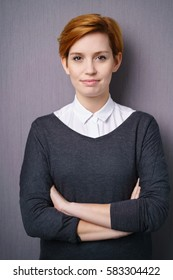 Young woman with short red hair wearing white blouse under dark sweater standing arms folded against purple wall, confidently looking at camera. Vertical portrait