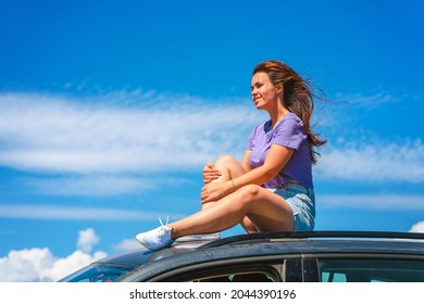 A young woman in shorts is sitting on the roof of a Volkswagen Tiguan car with a view of a beautiful blue sky with clouds. The concept of traveling by car.