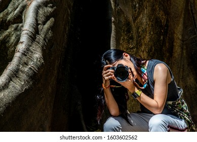 Young woman with Shoulder bag and using a camera to take photo Giant big tree, Size comparison between human and giant big tree in Ban Sanam of Uthai Thani Province, Thailand, nature background.