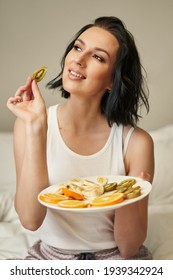 young woman with shoulder-length dark hair in light-colored pajamas holds a plate of sliced fruits and looks dreamily to the side