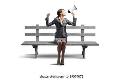 Young woman shouting into megaphone on wooden bench. Beautiful girl in business suit sitting on bench. Pretty businesswoman screaming with loudspeaker isolated on white. Promotion and announcement