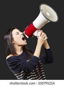 young woman shouting with a megaphone against a black background
