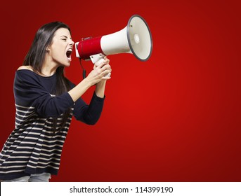 young woman shouting with a megaphone against a red background