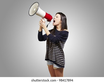 young woman shouting with a megaphone against a grey background
