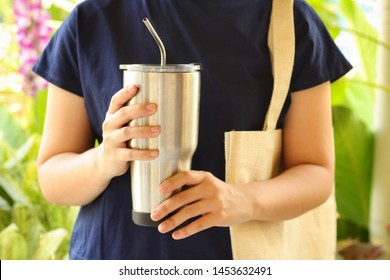 Young woman show reusable glasses of water in her hand with green garden background.Use water-glass and steel straw for Replacement plastic cup can save the earth.Reduce global warming concept.