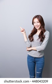 Young woman show something  and wearing jeans with isolated gray background, asian