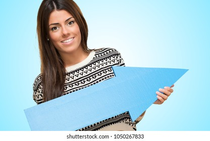 Young Woman Showing Arrow Sign against a blue background
