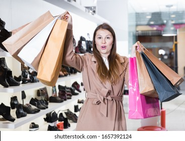 Young woman is showing bags with purchases in shoes store.