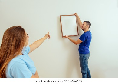 Young Woman Showing To Boyfriend For Hanging Picture Frame On Wall At Home. Young Family Moving In A New Home Concept.