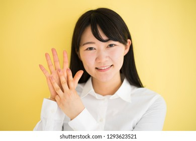 Young woman showing eight fingers against yellow background