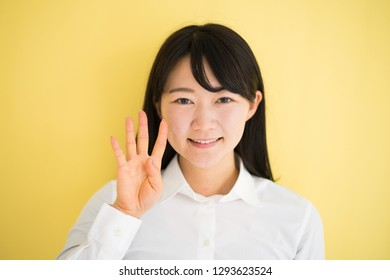 Young woman showing four  finger against yellow background