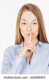Young woman showing hand silence sign, asking someone to keep it quiet. human emotion expression and lifestyle concept. image on a white studio background.