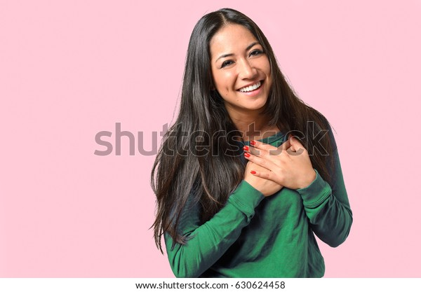 Young woman showing her heartfelt gratitude and thanks clasping her hands to her heart with a pleased smile on, isolated on pink