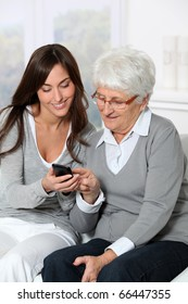 Young woman showing how to use mobile phone to grandmother