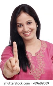 Young woman showing index finger against white background