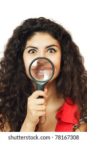 Young woman showing lips through magnifying glass