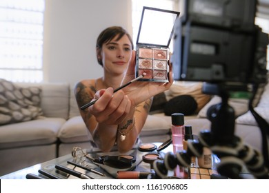 Young woman showing a makeup palette on camera and recording her video. Woman making a video for her beauty blog on cosmetics.