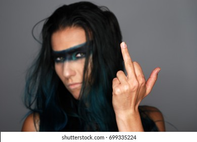 Young woman showing middle finger, posing with professional make-up selective focus