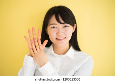Young woman showing nine fingers against yellow background