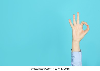 Young woman showing OK gesture on color background. Space for text