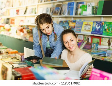 young woman showing open book to girl in school age in book boutique