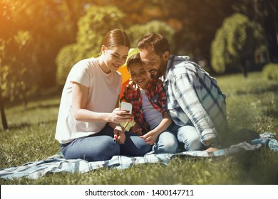 Young Woman Is Showing Photos On Phone To Her Husband And Daughter While Sitting On The Blanket In The Park. Family Is Smiling. Family Day.