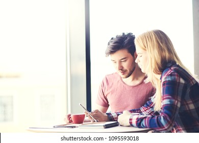 Young woman showing pictures on smartphone to her male colleague during coffee break at cafe
