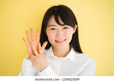 Young woman showing seven fingers against yellow background