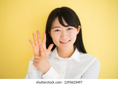 Young woman showing six fingers against yellow background