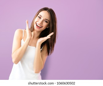 Young woman showing smile, in casual smart clothing, over purple background, with copyspace for slogan, advertising or text message