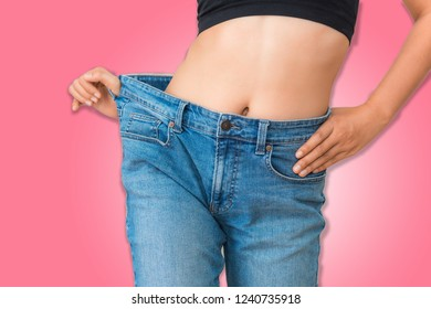 Young woman showing successful weight loss with her jeans on isolate background., Healthcare, Diet concept