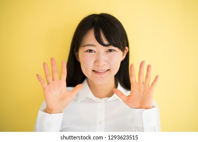 Young woman showing ten fingers against yellow background