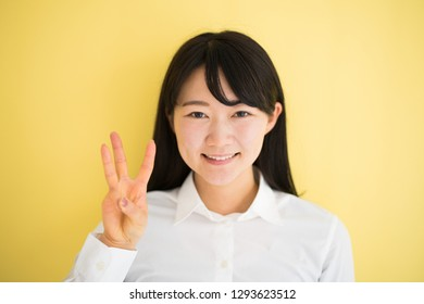Young woman showing three fingers against yellow background