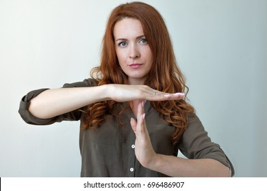 Young woman showing time out hand gesture, frustrated screaming to stop isolated on grey wall background.