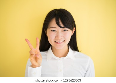 Young woman showing two fingers against yellow background