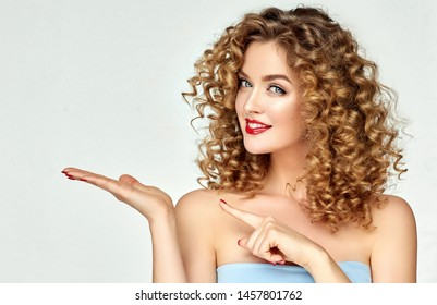 Young woman shows and advertises some product .Beautiful girl  pointing to the side . Presenting your services. Expressive facial expressions emotions