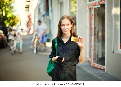 young woman shows a credit card and holds a mobile phone in the background on a city background.