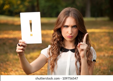 A young woman shows an exclamation point and threatens