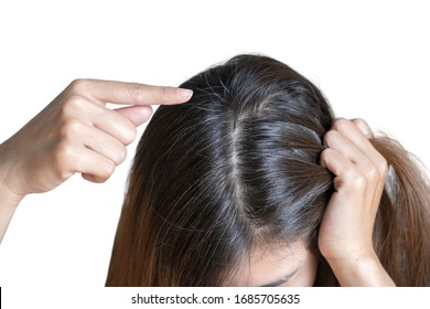 Young woman shows her black gray hair roots on white background